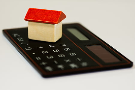 black calculator with white and red wooden house table decor