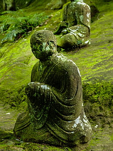 sitting monk statue with algae during daytime
