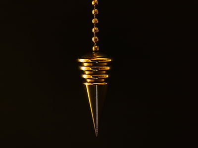 macro photography of gold pendant