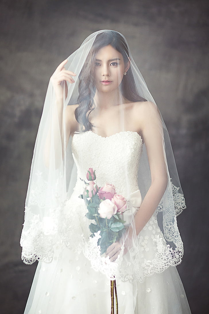 woman wearing white wedding gown holding bouquet of flowers