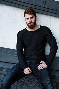 man wearing black long-sleeve shirt leaning on wall