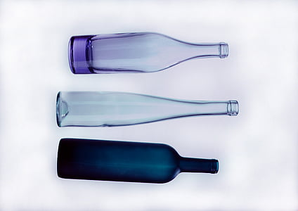 purple, black, and clear glass bottles with white background photo