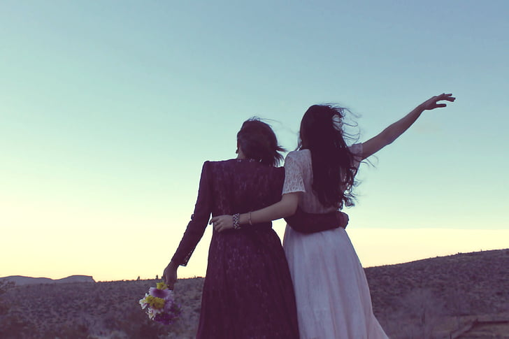 two women standing under the cliff during daytime