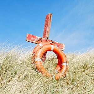 red wooden cross and two orange swim rings