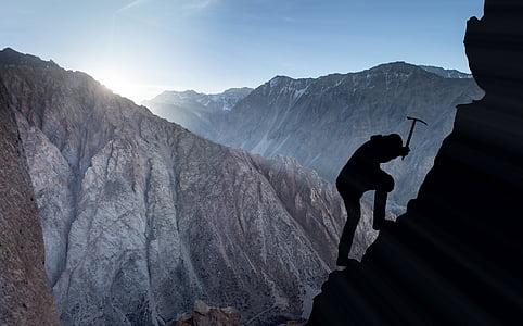 person climbing on mountain silhouette photo