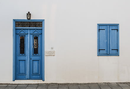 white concrete wall with blue door and window