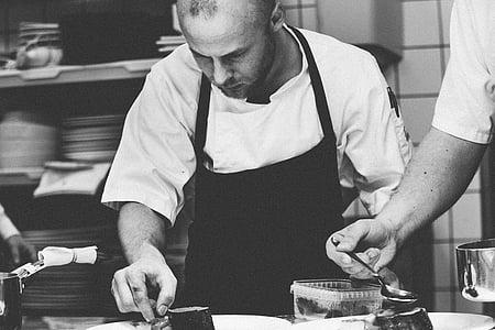 grayscale photo of man wearing apron