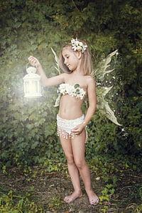 girl wearing fairy costume holding lantern