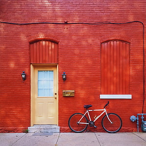 white mountain bike parked beside red painted bricked wall