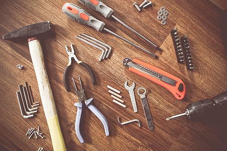 assorted handheld tools on wooden parquet
