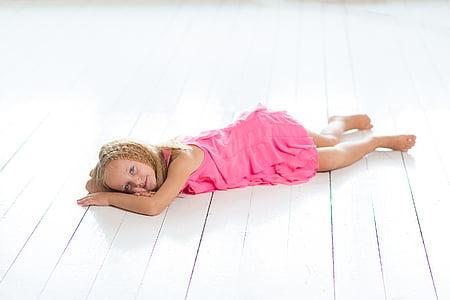 braided blonde girl wearing pink dress lying on floor