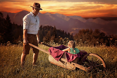 girl riding wooden wheelbarrow during sunset