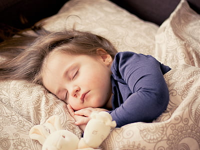 toddler wearing black long-sleeved shirt sleeping on brown bed comforter set