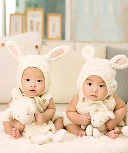 two babies in white rabbit costumes