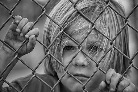toddler in gray metal fence
