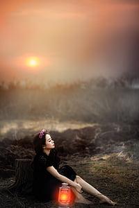 woman sitting on the ground beside the kerosene lamp
