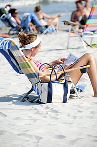 woman in pink striped bikini top sitting on blue striped beach chair