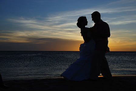silhouette of dancing man and woman on shore during sunset