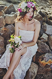 woman wearing white lace tube dress sitting on rock holding white flower bouquet