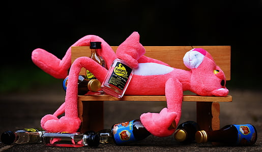 pink panther plush toy laying on brown wooden bench near liquor bottles
