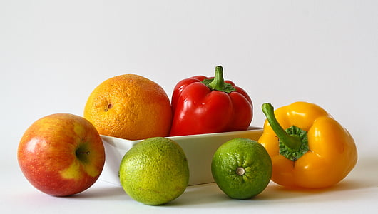 two bell peppers and four fruits on white surface