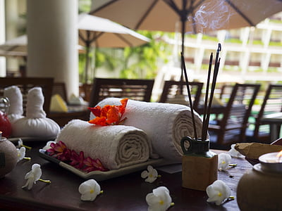 two rolled white towels on brown wooden surface with white petaled flowers