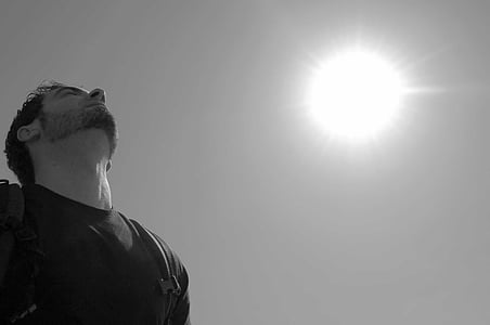 grayscale photo of man wearing t-shirt carrying backpack under sun