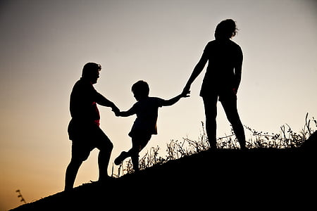 silhouette of family on hill during twilight