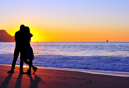 silhouette of man and woman beside body of water