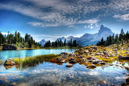 body of water near trees and mountains at daytime