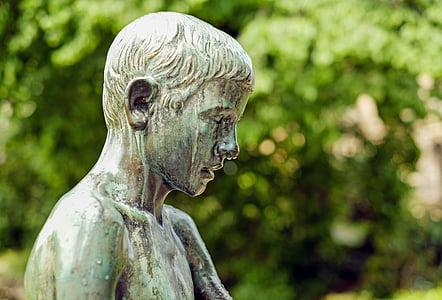 topless boy statue near green trees