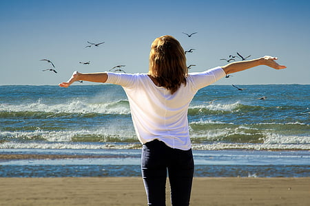 woman wearing white shirt and black pants on beach