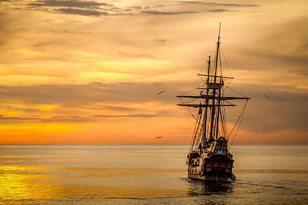 brown and black galleon ship on body of water at golden hour