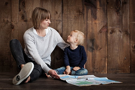 woman and child seats on brown wooden surface