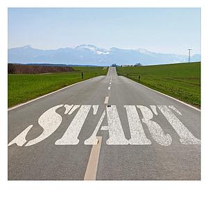 white start text on black asphalt road