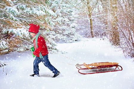 child in red long-sleeved winter top pulling brown and red snow sled