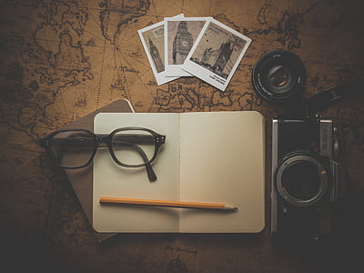 eyeglasses, pencil, planner, camera, and photos on brown map
