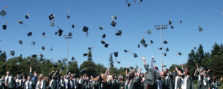 students throwing mortar boards in open field at daytime