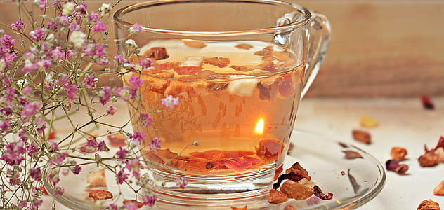 photo of filled clear glass teacup with saucer and flower petals