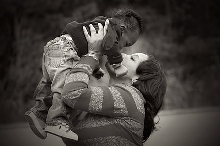 woman holding baby up high