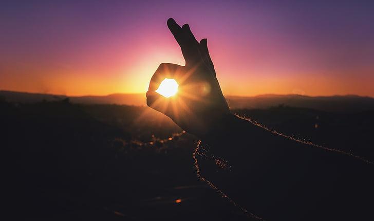 silhouette photo of okay hand sign through sunrise