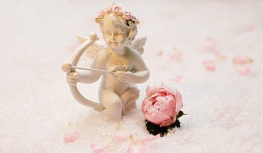 cupid beside rose bud
