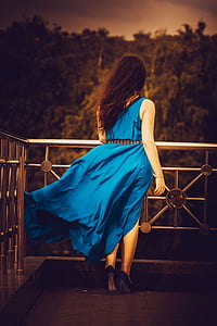 woman wearing blue sleeveless dress and black heels standing beside gray metal railings