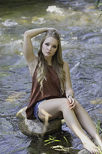 woman in red tank top sitting on brown stone