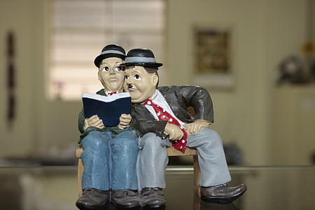 man sitting beside man while holding book