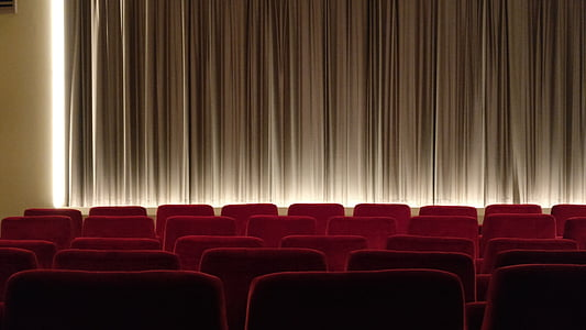 empty theater covered with brown curtain and red chairs