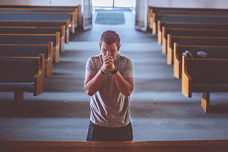 man praying inside the church