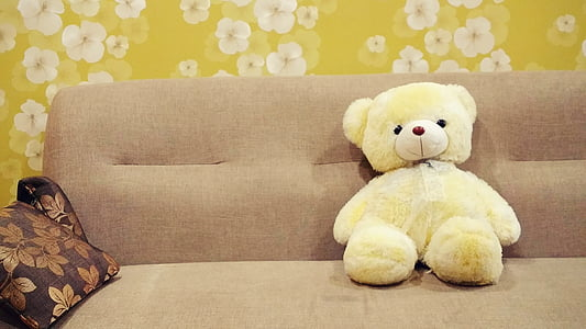 white bear plush toy on brown fabric sofa