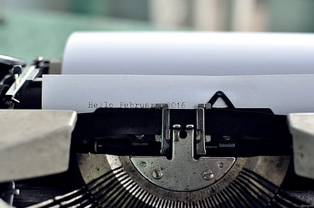 close-up photo of black typewriter with white paper