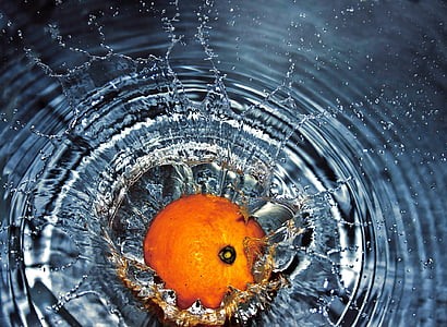 orange fruit drops on water
